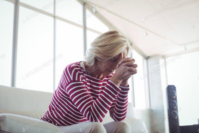 Depressed businesswoman sitting on sofa