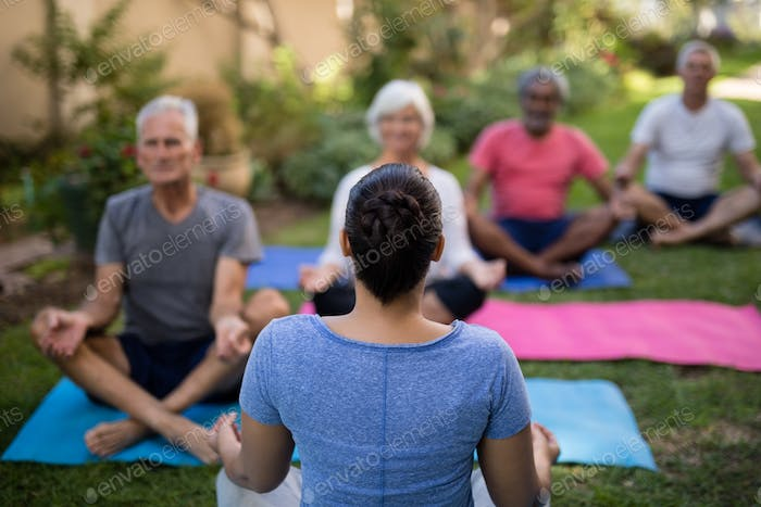 Trainer guiding senior people in meditating exercise