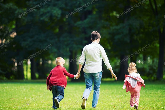 happy family playing together outdoor in park