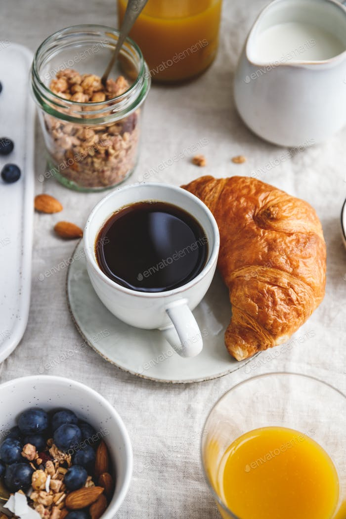 Breakfast table with coffee, croissant, granola, nuts, berries and milk