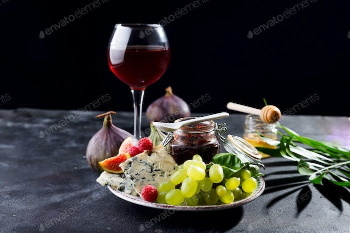delicacy blue cheeses, fruit and jam in jar with red wine in glass and honey, palm leaf