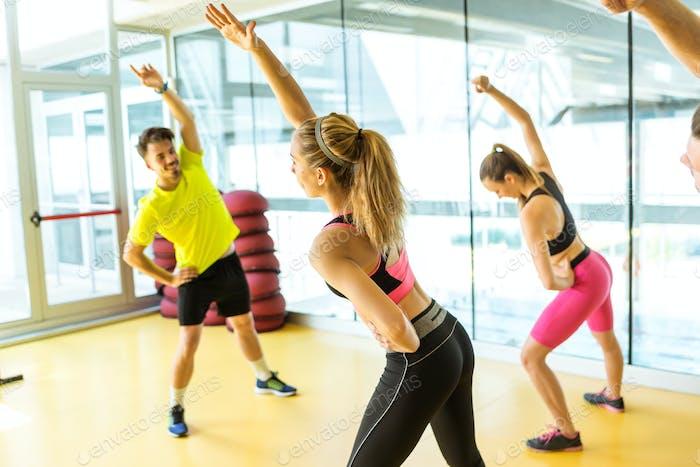 Gruppe von sportlichen Menschen, die Aerobic-Unterricht auf einem Fitness-Center machen.