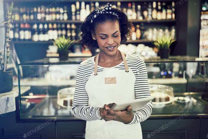 Smiling African entrepreneur working in her cafe with a tablet