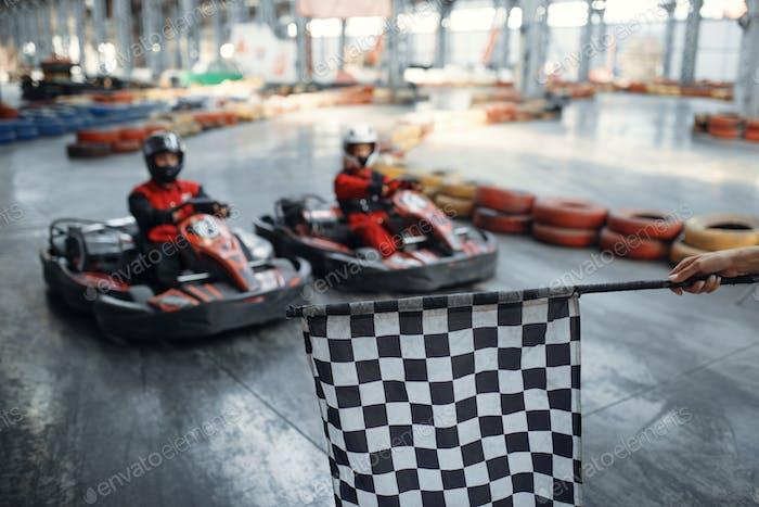 Two kart racers on start line, checkered flag