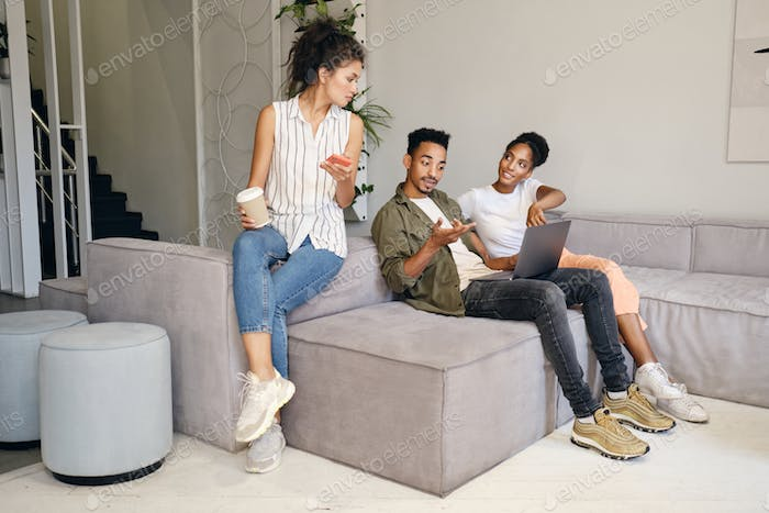 Group of young multinational casual people working together on laptop in modern co-working space