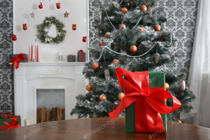 Christmas present in decorated room background, holiday concept