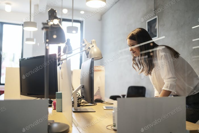 Portrait of young frustrated businesswoman overworked in office