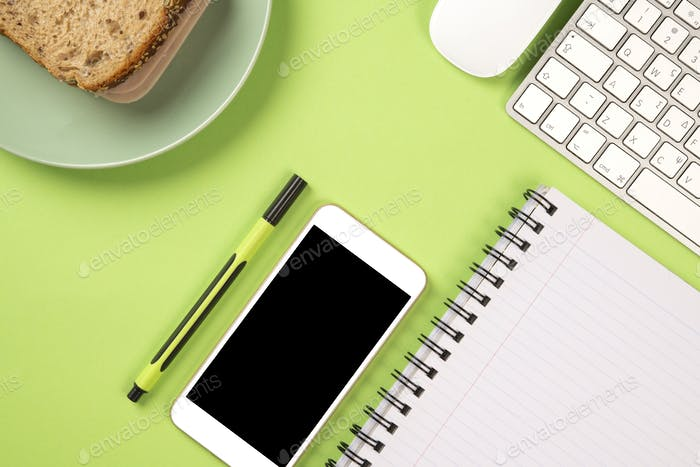 Light green color office with toast breakfast and stationery supplies