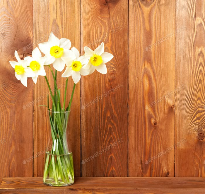 Bouquet of fresh flowers, daffodils in vase on wooden table, opposite brown wooden wall