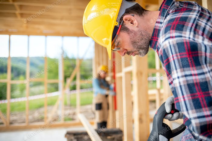 Focused worker using tools at building site of wooden house