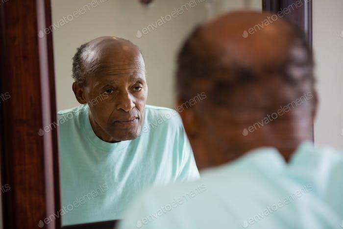 Spiegel mit Reflexion des betroffenen älteren Mannes