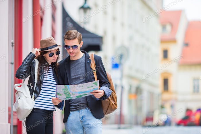Young tourist couple traveling on holidays outdoors smiling happy. Caucasian family with city map in