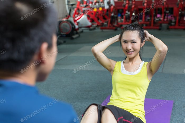 Professional fitness coach training fit woman in the gym