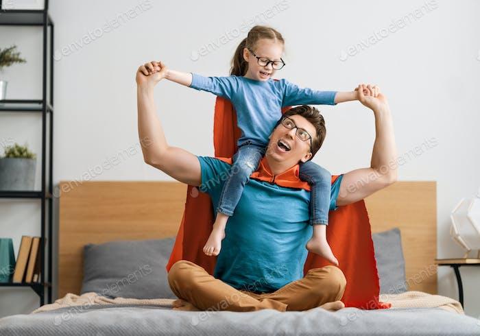 Mädchen und Papa im Superhelden-Kostüm