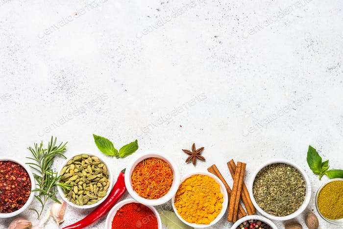 Spices and herbs on white stone table