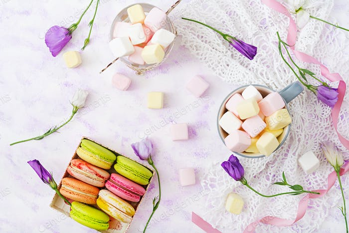 Colorful macaroons and marshmallows on a light background. Flat lay. Top view