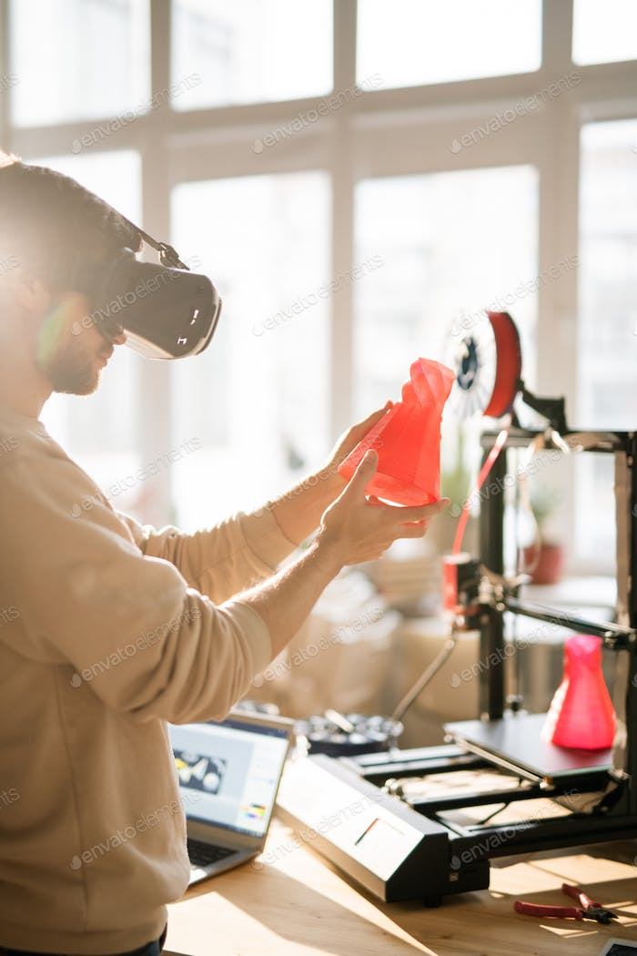 Young businessman in vr headset holding red plastic object in front of himself