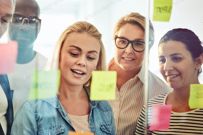 Smiling businesspeople brainstorming with sticky notes on a glass wall
