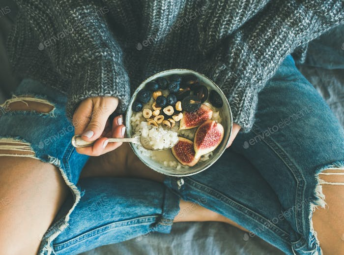 Woman in shabby jeans and sweater eating healthy breakfast