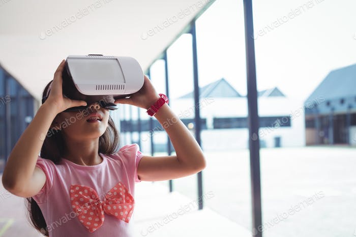Schoolgirl using virtual reality glasses in corridor