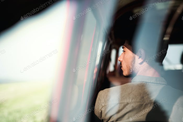 A young man sitting in a car on roadtrip through countryside, shot through glass.
