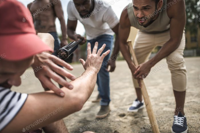 group of multiethnic men attacking other one with baseball bats
