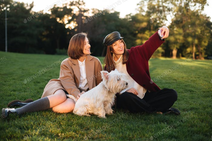 Beautiful girls taking selfie on cellphone while spending time with cute dog in park