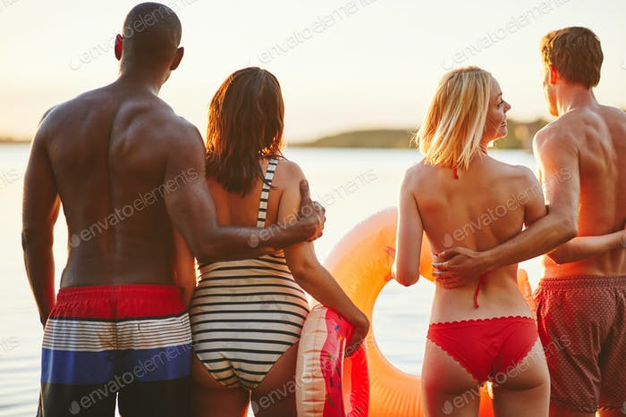 Two diverse young couples in swimwear watching the sunset together