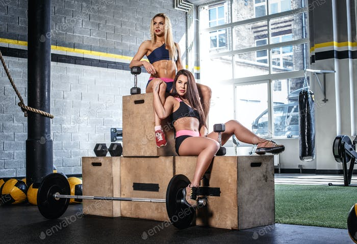 Two women posing on a winner's podium in a gym club.