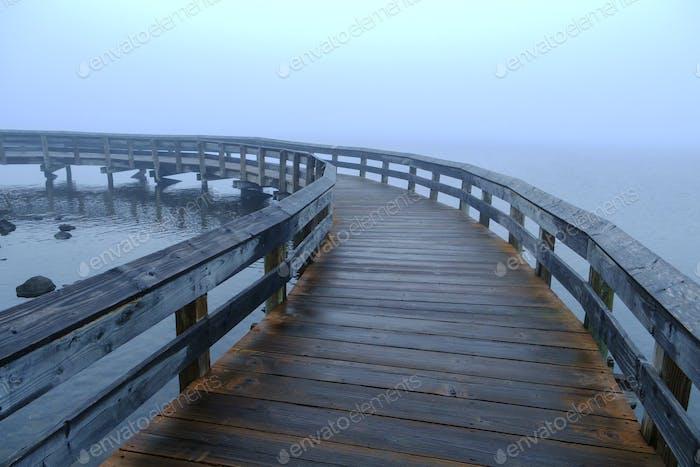 Curving boardwalk in fog