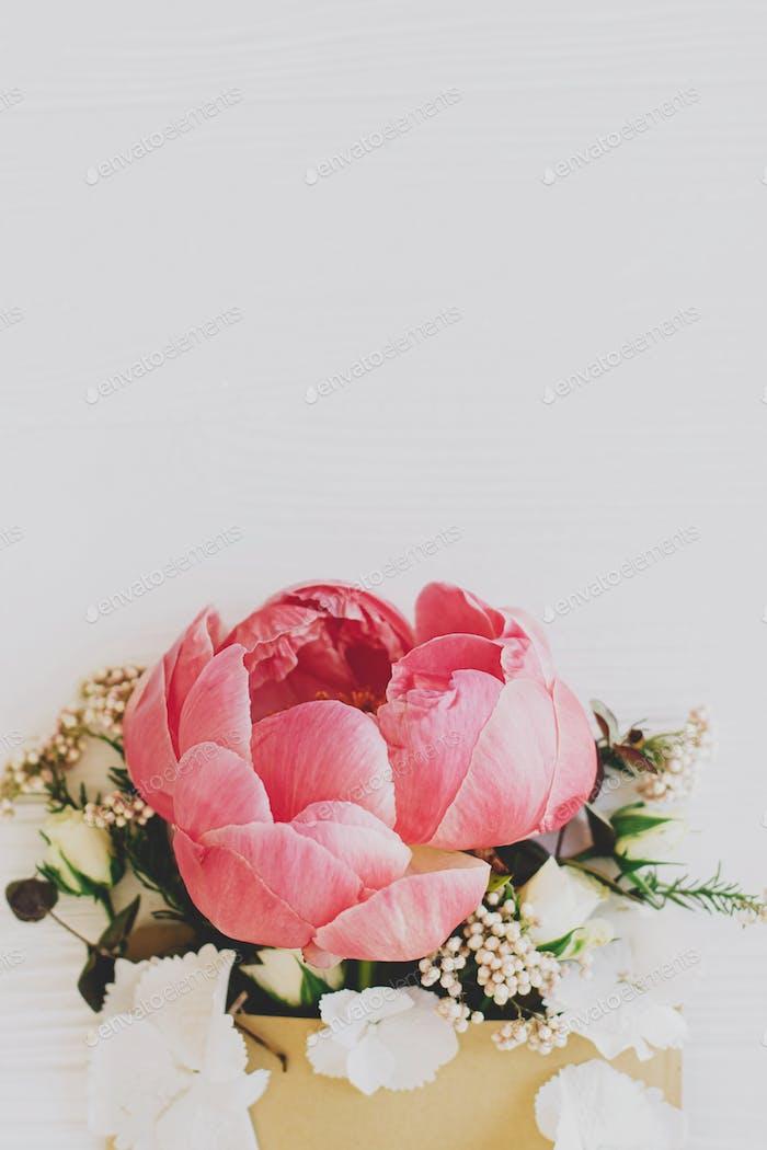 Творческая цветочная открытка, пион, белые цветы и эвкалипт в ремесленном конверте на белом дереве