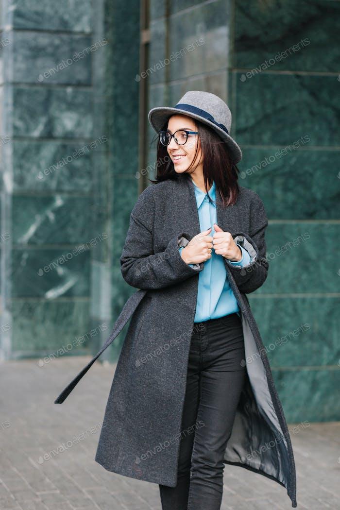 Stylish city portrait fashionable young woman walking in long grey coat on street. Wearing hat, blac