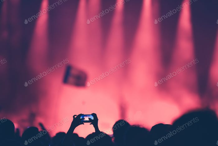 Fan taking photo of concert at festival with a smart phone