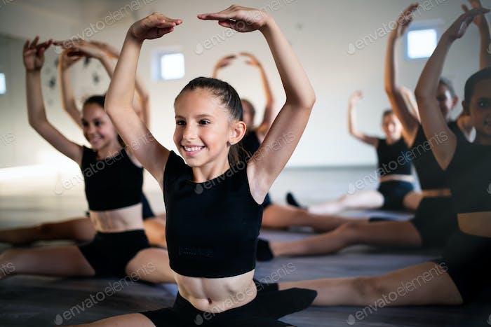 Gruppe von fit glückliche Kinder trainieren Ballett im Studio zusammen