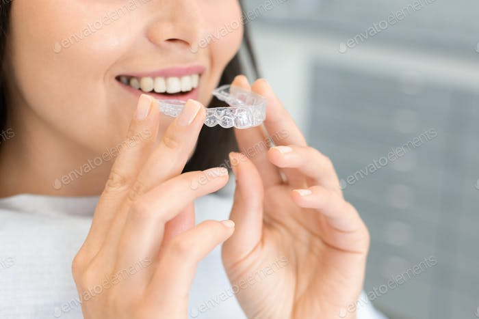 Girl holding invisible braces, moder teeth trainer