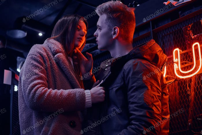 Young stylish couple wearing warm clothes standing on the staircase to the underground nightclub