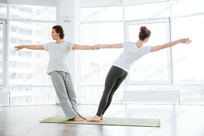 Young couple doing stretching exercises in yoga studio together