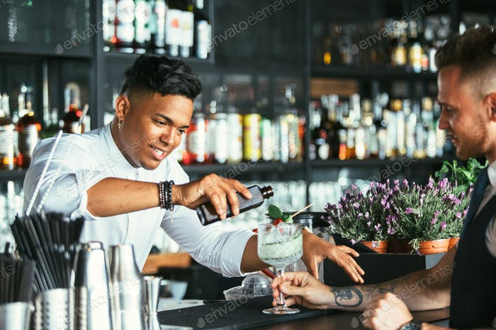 Bartender prepares a cocktail to a waiter