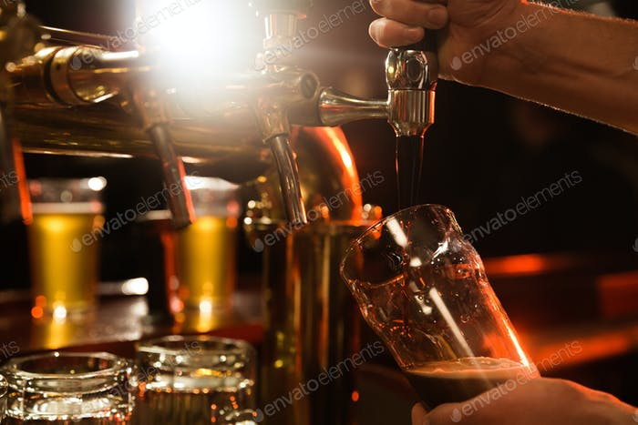 Nahaufnahme eines Barkeeper gießt Bier