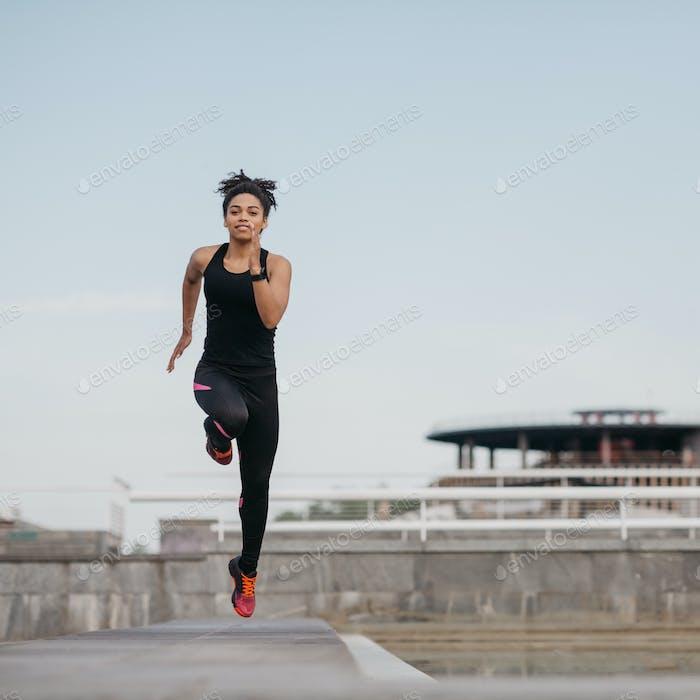 Laufen mit Sprüngen im Training. Afroamerikanisches Mädchen in Sportuniform im Sprung, auf dem Stadion