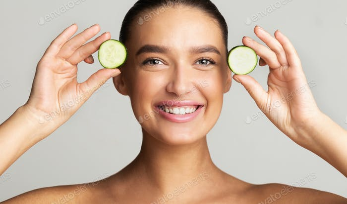 Young playful woman holding pieces of cucumber