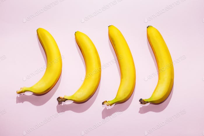 Bananas on pink pastel background. minimal idea food concept
