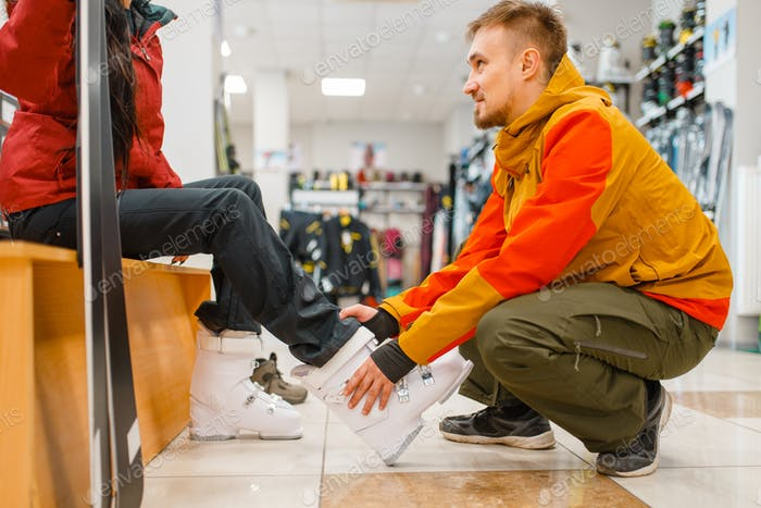 Man helps woman to trying on ski boots, shopping