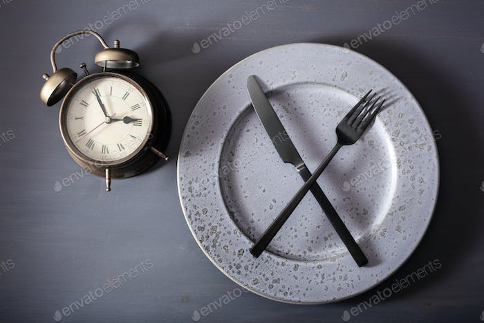 concept intermittent fasting, ketogenic diet, weight loss. fork and knife crossed plate alarmclock