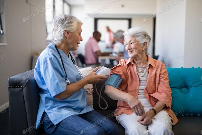 Nurse checking senior woman blood pressure at nursing home