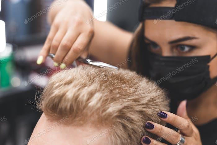 Frauen Friseur macht flache Spitze Haarschnitt mit einer Schere einen bärtigen Mann. Service in einer Maske von Virus.