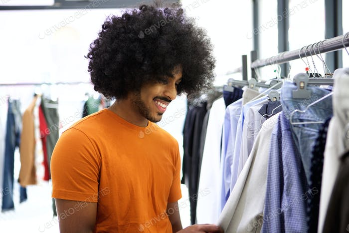 Man with afro looking for clothes in store