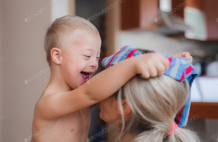 A laughing handicapped down syndrome child with his mother indoors having fun.