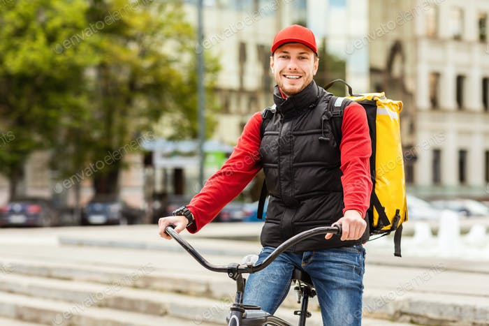 Delivery Guy Smiling To Camera Posing With Bicycle In City