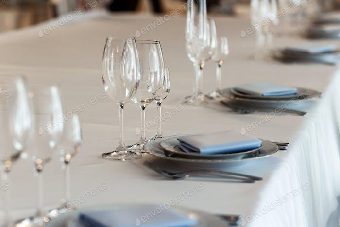 luxury wedding arrangement of stylish glasses plates on napkins